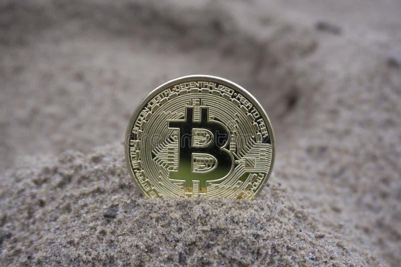 Guld- bitcoinmynt i sanden arkivbild