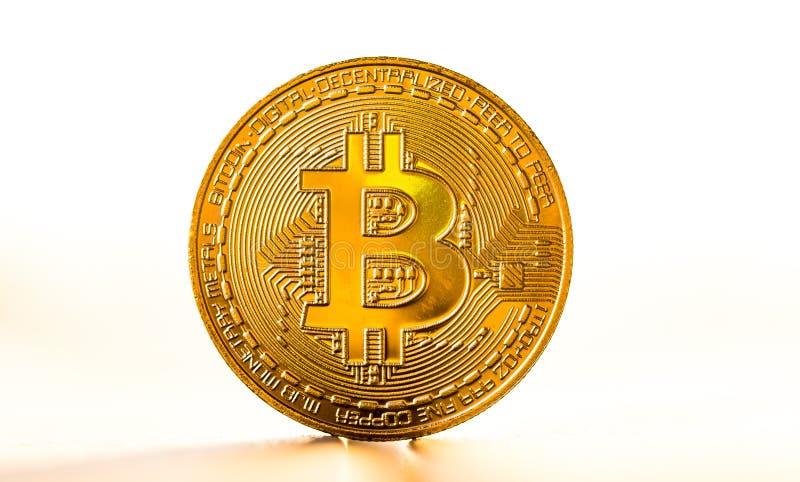Guld- bitcoinmynt som förläggas på vit bakgrund i ljuset av solnedgången Faktiskt valutasymbol royaltyfri fotografi