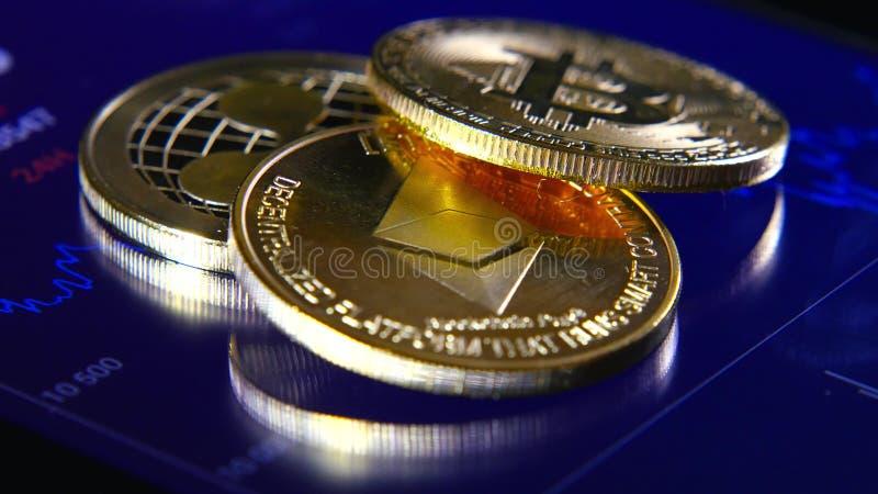 Guld- bitcoins på bakgrunden av ett grafiskt materiel kartlägger Koncentrationen av Crypto-valutan av faktiska pengar arkivfoto