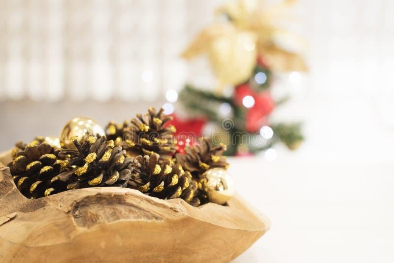 Guld- blänka kottar i en stor träbunke på en vit trätabell På en bakgrund av en julgran med ljus arkivbild