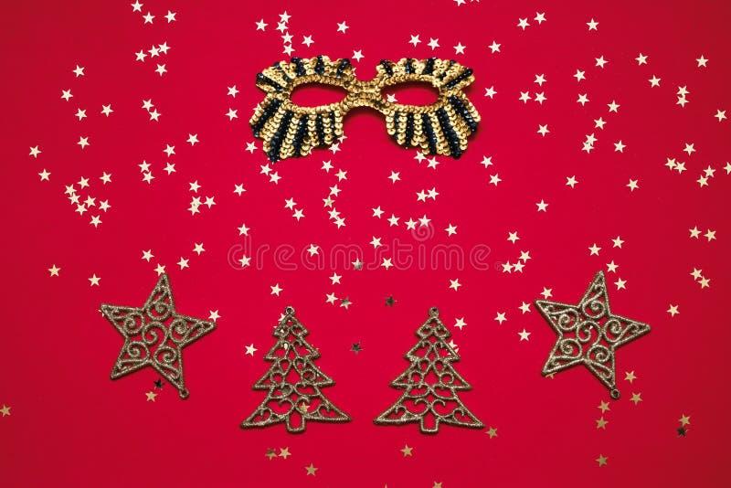 Guld- blänka maskering och julprydnader med guld- stjärnor på röd bakgrund Bästa sikt, kopieringsutrymme royaltyfri bild