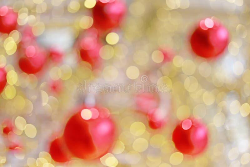 Guld- bokehsuddighetsbakgrund och röd boll arkivbild
