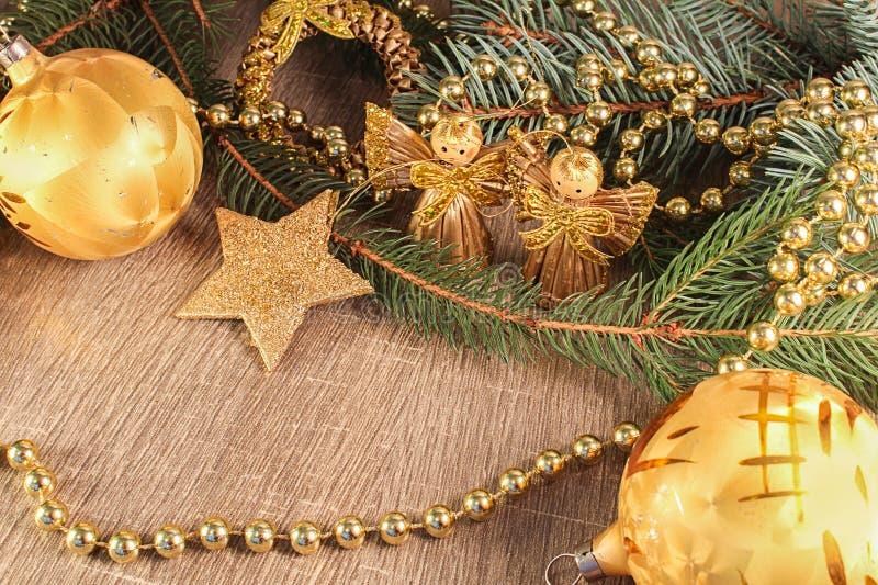 Guld- boll, stjärna och änglar med den barrträds- filialen på wood backgr royaltyfri fotografi