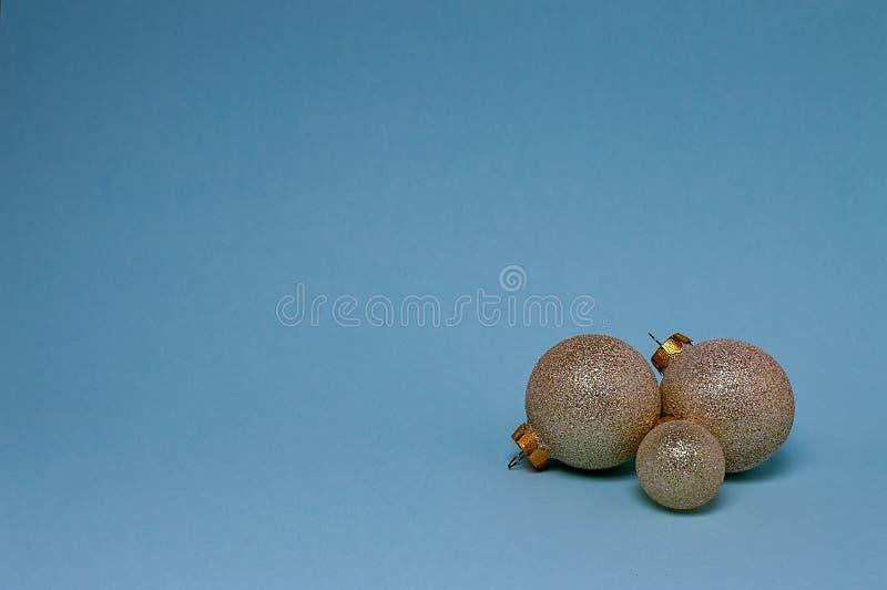 Guld- bollar för jul på en blå bakgrund, närbild royaltyfria bilder