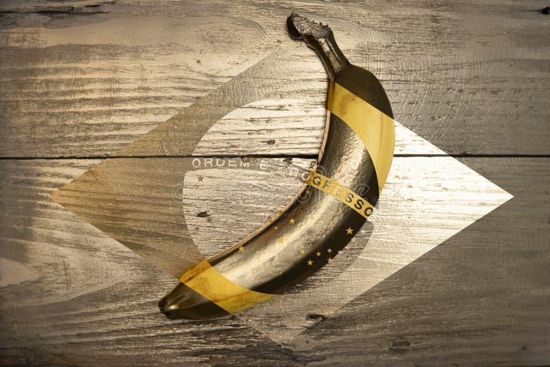 Guld- brasiliansk banan på träbakgrund Blandat massmedia royaltyfri foto