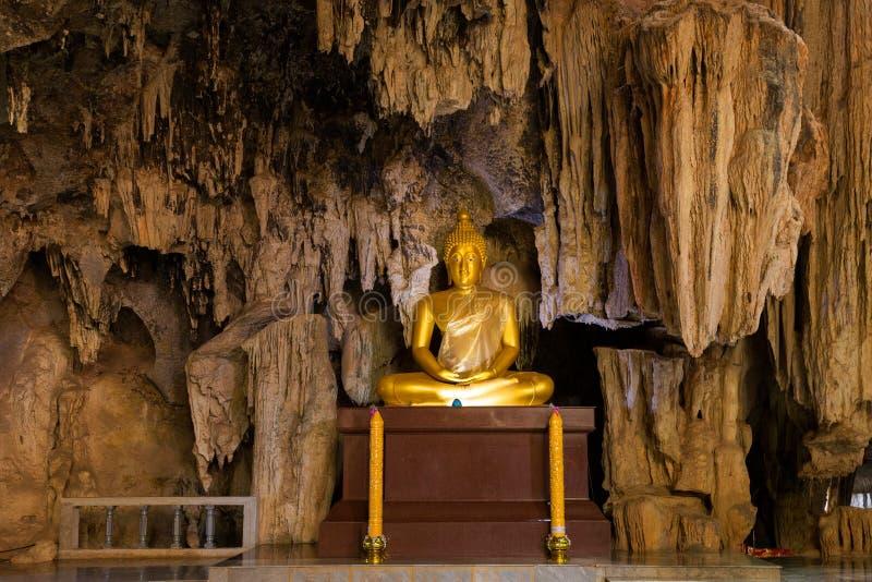 Guld- Buddha staty i grotta arkivbild