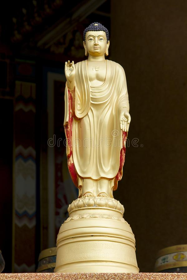 Guld- Buddhastaty i anseendeställing royaltyfria foton