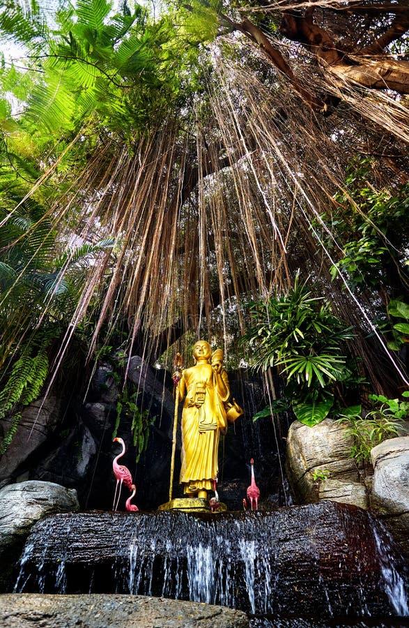Guld- Buddhastaty i trädgården arkivbild