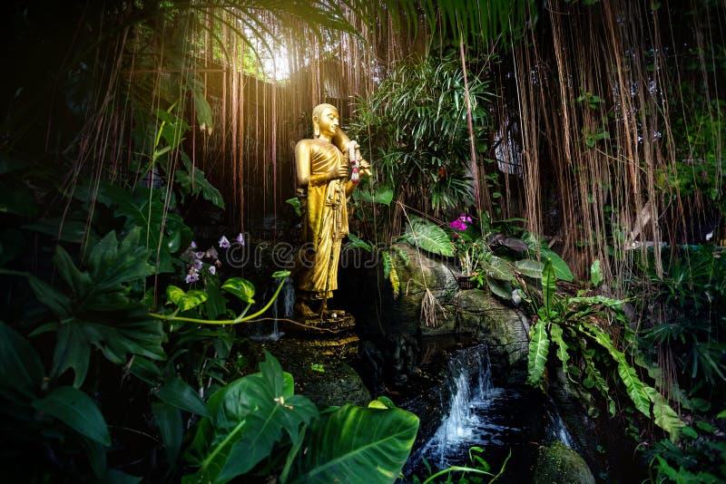 Guld- Buddhastaty i trädgården royaltyfri foto