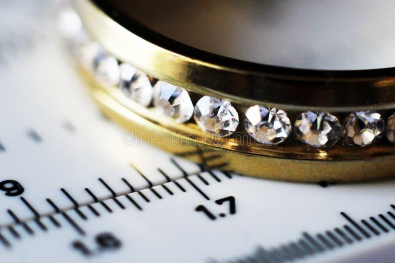 Guld- cirkel med diamanter och ett mäta instrument, värdet av smycken royaltyfri foto