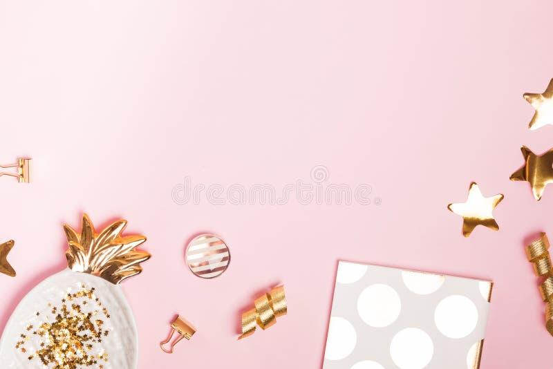 Guld- dekor och kvinnlig tillbehör på den rosa bakgrunden, royaltyfri foto