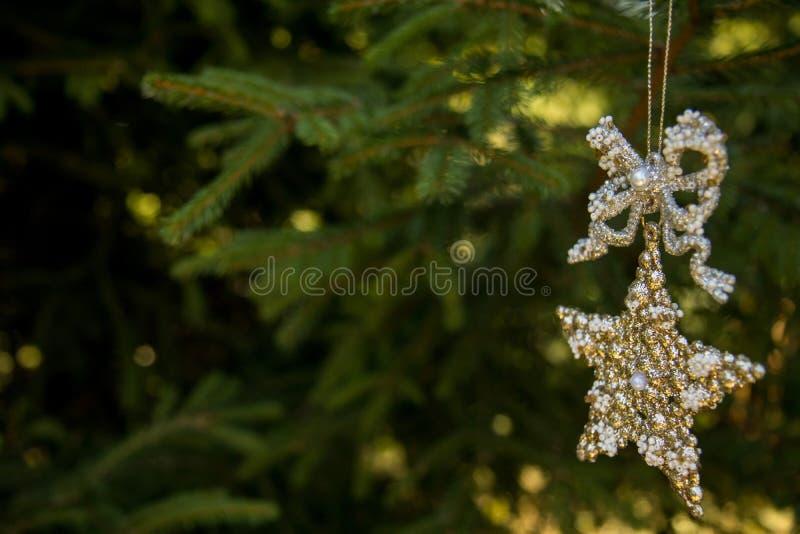 Guld- dekorativ stjärna i band på suddig brach av xmas-trädet Glad julkort Tema för vinterferie lyckligt nytt år arkivfoto