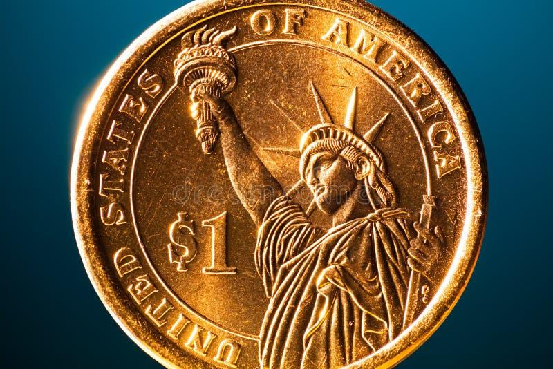 Guld- dollarmynt på blå bakgrund arkivbilder