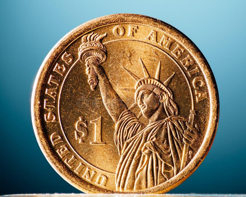 Guld- dollarmynt på blå bakgrund arkivbild