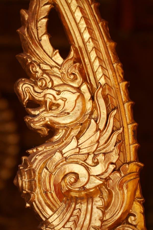 Guld- drakestaty för närbild i den thailändska templet, bronssouvenir som tillverkar produkten i mörka bakgrunder royaltyfri bild
