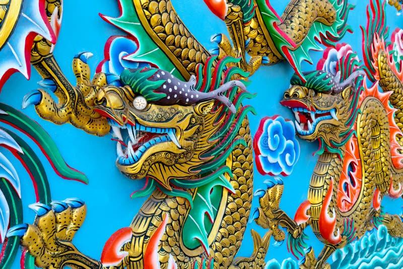 Guld- drakestaty på väggen på templet i Thailand, kinesisk stil royaltyfri fotografi
