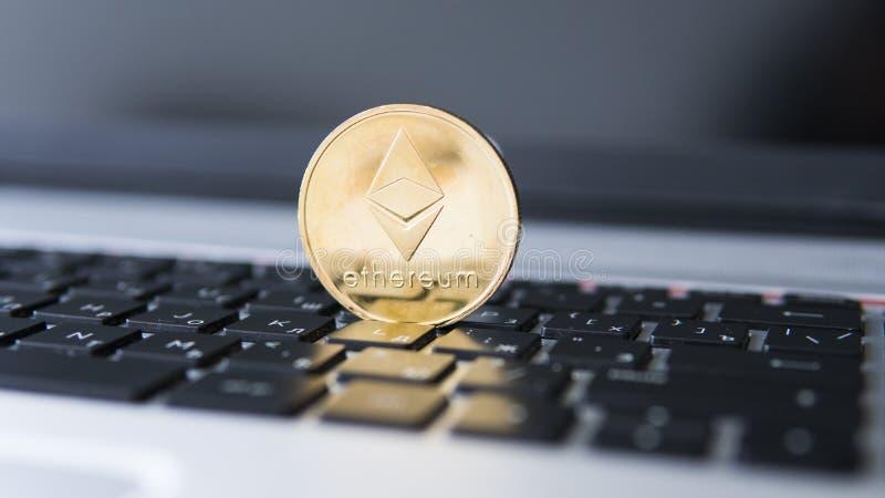 Guld- Ethereum mynt på en bärbar dator Ethereum crypto valuta på ett bärbar datorsvarttangentbord Digital pengar och faktiskt royaltyfri bild