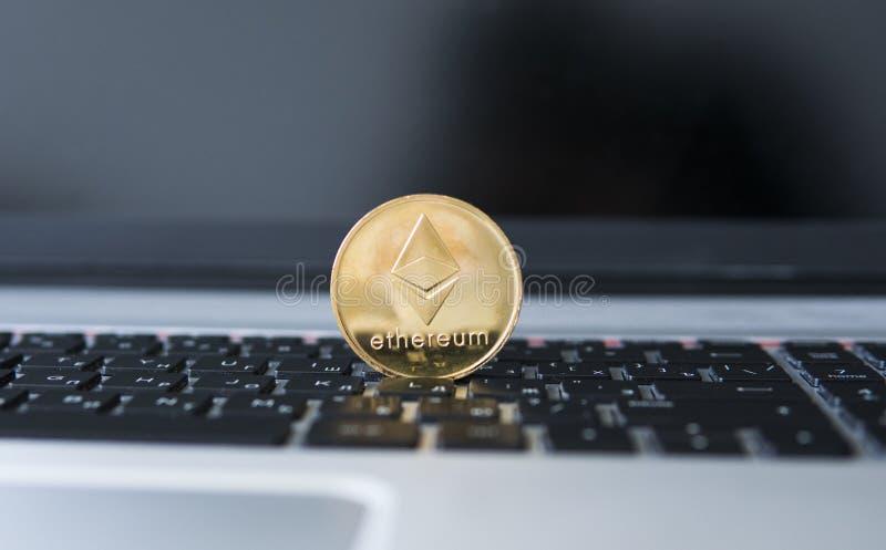 Guld- Ethereum mynt på en bärbar dator Ethereum crypto valuta på ett bärbar datorsvarttangentbord Digital pengar och faktiskt arkivfoton