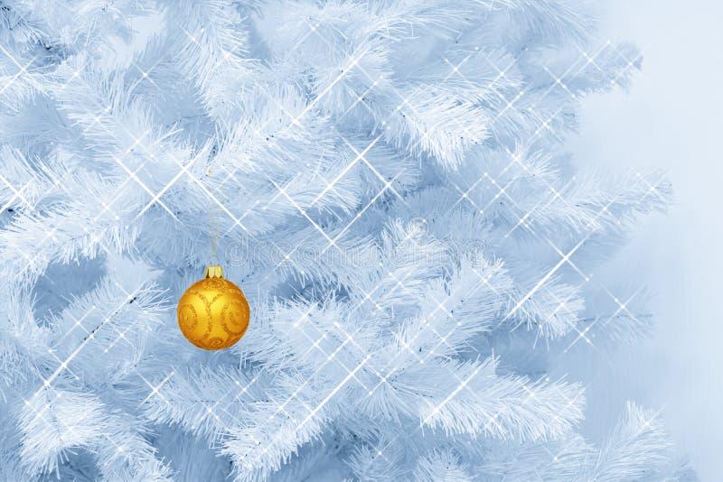 Guld- exponeringsglas blänker garnering för prydnadjulstruntsaken som hänger på en blått tonad julgran royaltyfri foto