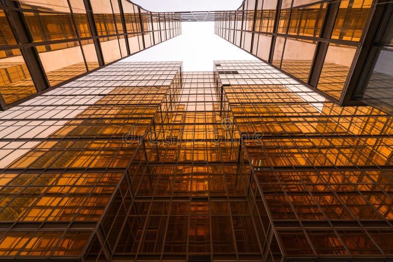Guld- exponeringsglasspegel av höghusaffärsbyggnader arkivfoto