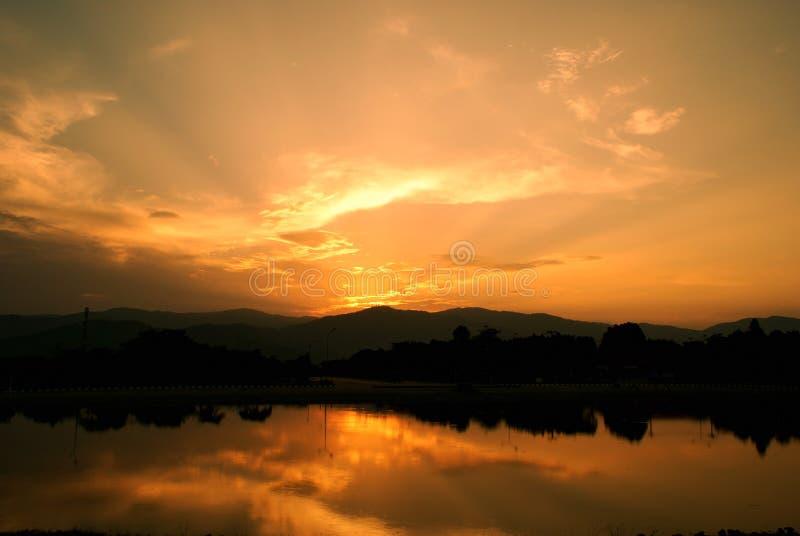Guld- färg av molnhimmel på skymningtid med sjön arkivfoto