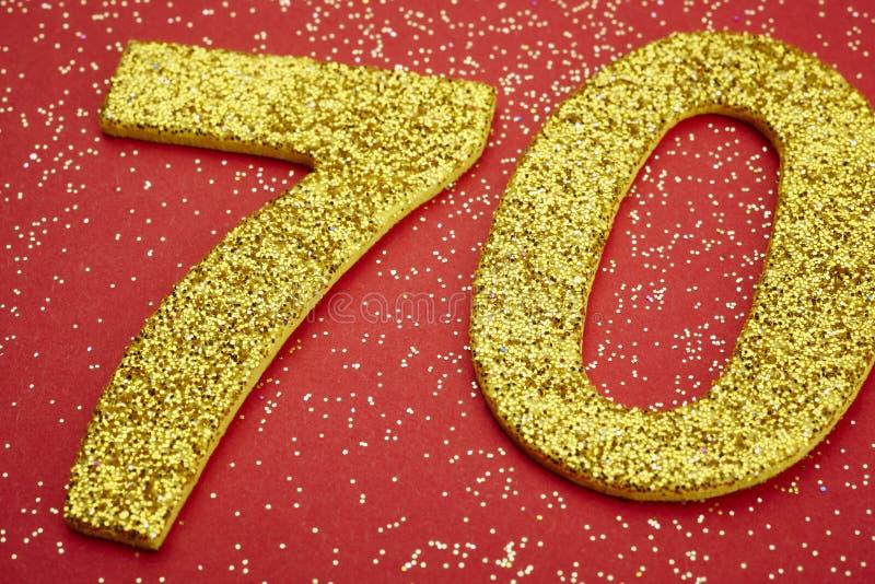 Guld- färg för nummer sjuttio över en röd bakgrund årsdagen royaltyfri illustrationer
