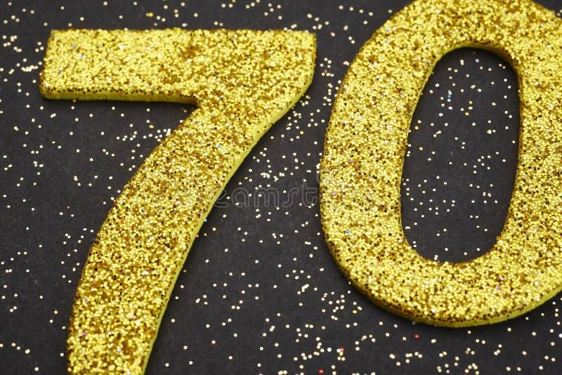 Guld- färg för nummer sjuttio över en svart bakgrund årsdagen stock illustrationer