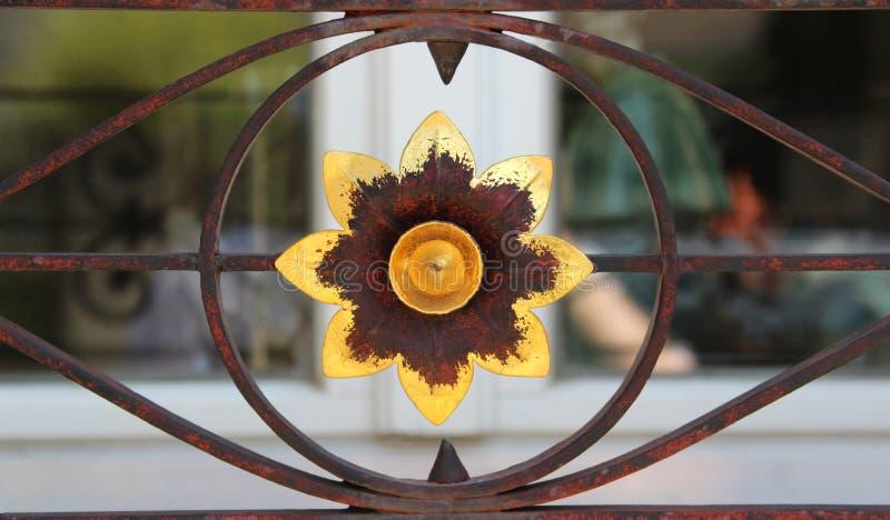 Guld färgad blomma, rostig dekorativ ironwork arkivfoton