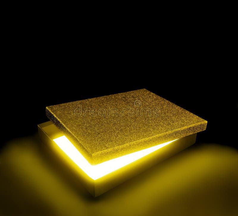 Guld- färggåvaask Öppnad ask mot svart bakgrund med c royaltyfri foto