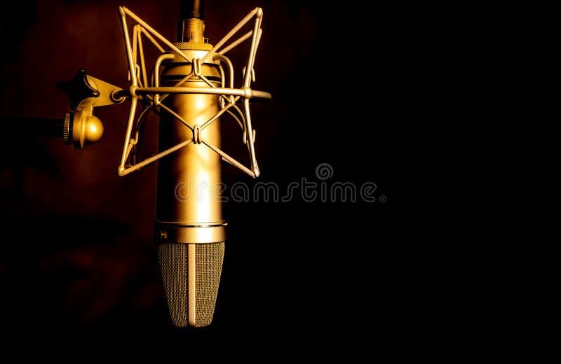 Guld- färgmikrofondetalj i musik och den solida anteckna studion, svart bakgrund, closeup fotografering för bildbyråer
