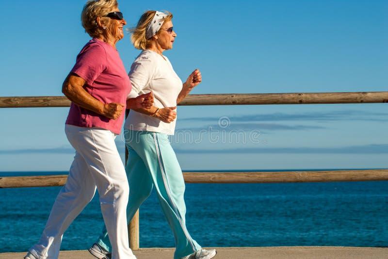 Guld- flickor som joggar längs beachfront. royaltyfria bilder