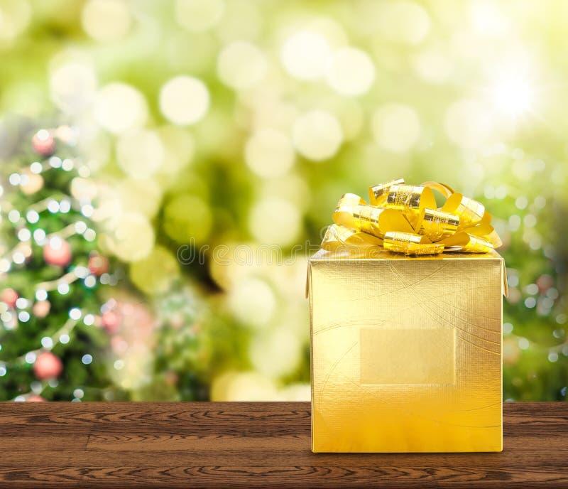 Guld- gåva på den bruna wood tabellen med julträd suddigt b royaltyfria foton