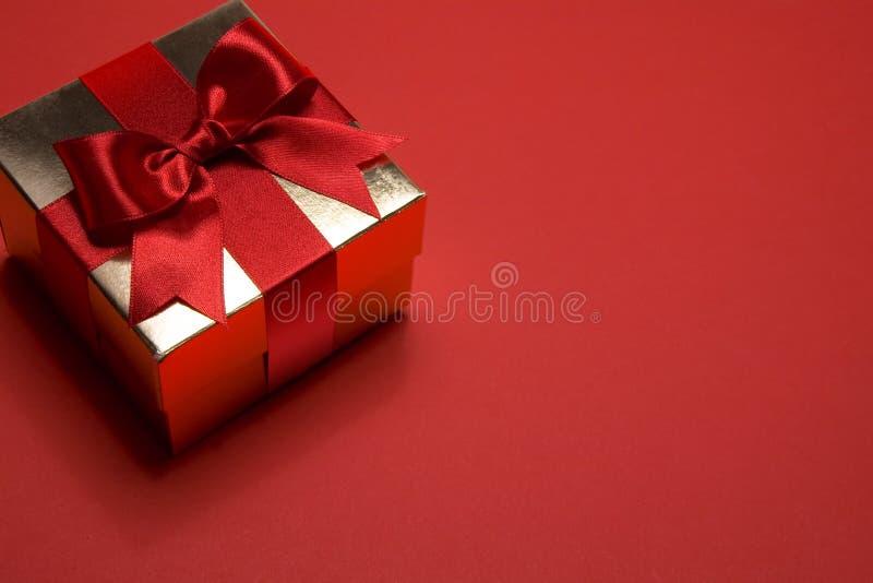 Guld- gåvaask på röd bakgrund royaltyfria foton