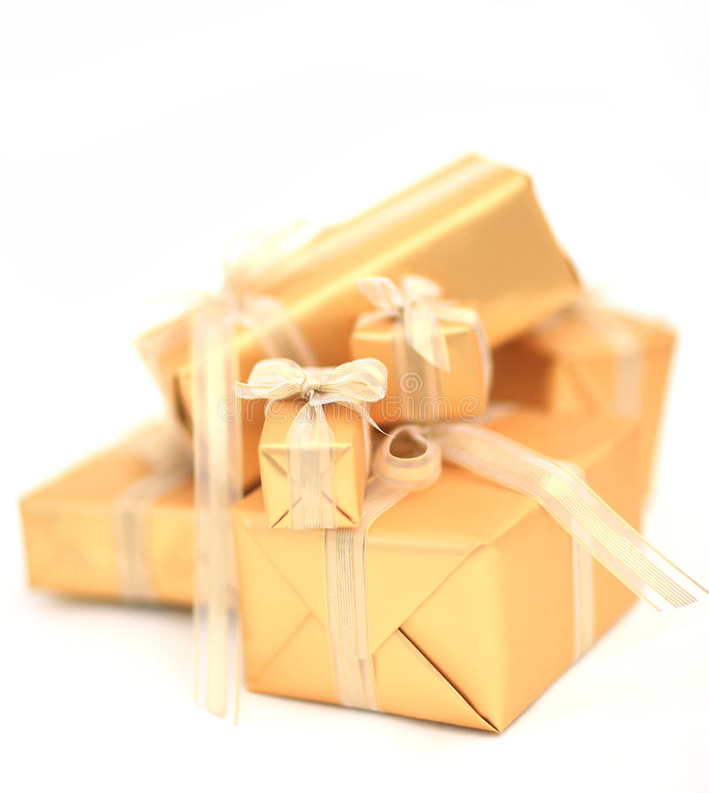 Guld- gåvaaskar med det guld- bandet på vit bakgrund arkivfoton
