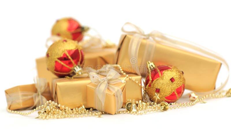 Guld- gåvaaskar med guld- band- och chrismasbollar royaltyfria bilder