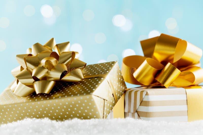 Guld- gåvor eller gåvaaskar på magisk bokehbakgrund Feriesammansättning för jul eller nytt år arkivfoto