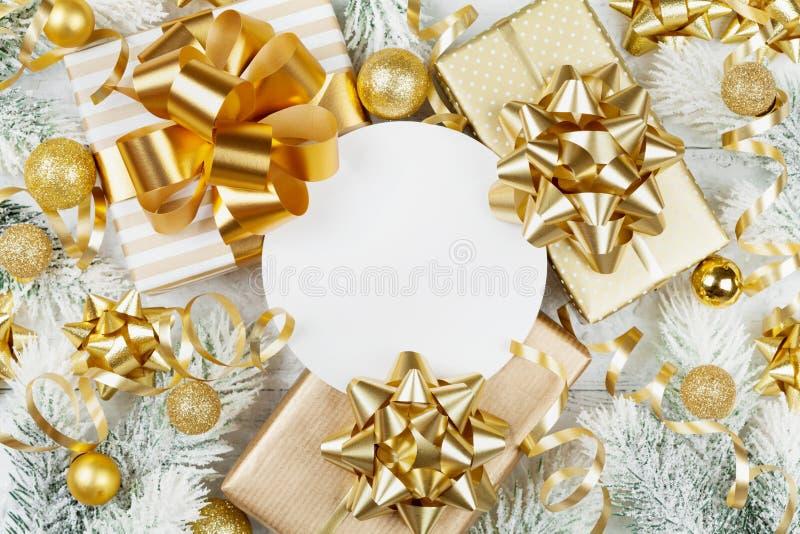 Guld- gåvor eller gåvaaskar, pappersmellanrum, snöig granträd och julgarneringar på den vita träbästa sikten för tabell Lekmanna- arkivfoto