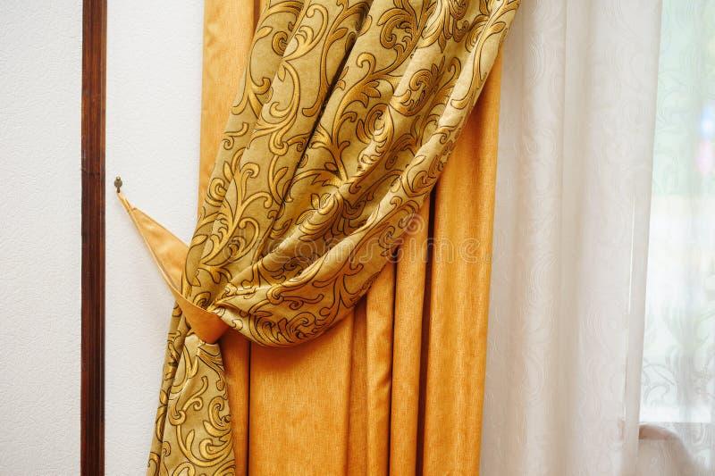 Guld- gardin på fönstret i rummet arkivfoton