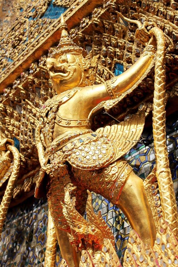 Guld- Garuda står på armen av väggen royaltyfri bild