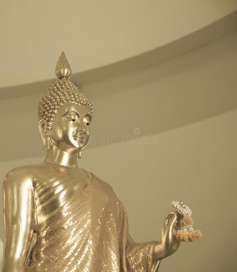 Guld- girland för ringblomma för Buddhastatyhåll royaltyfria foton