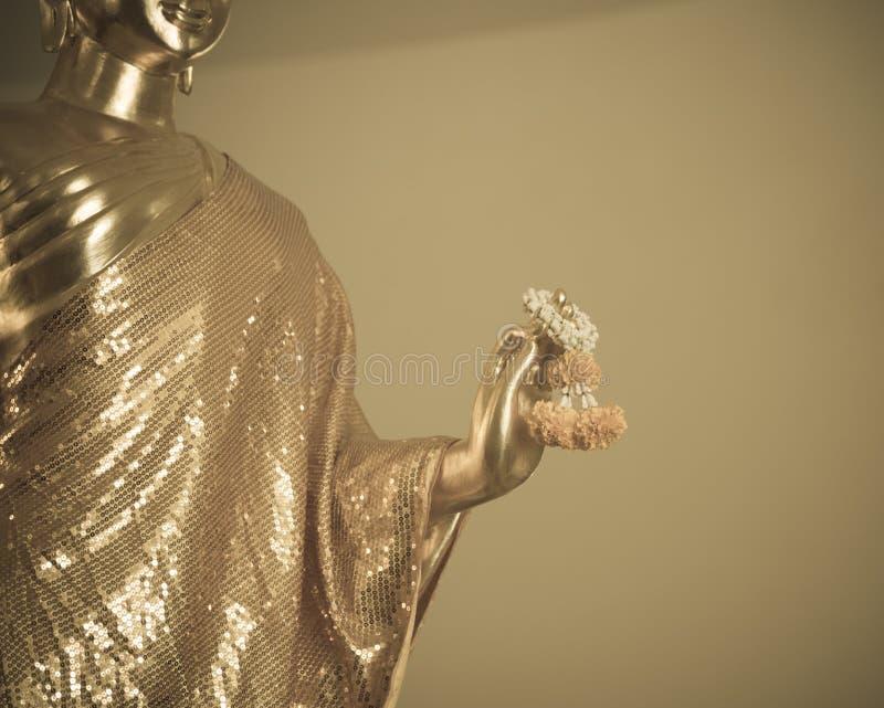 Guld- girland för ringblomma för Buddhastatyhåll royaltyfri foto
