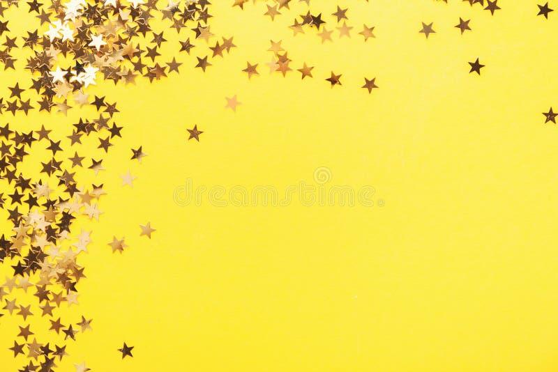 Guld- glänsande stjärnakonfettier på guling royaltyfri bild