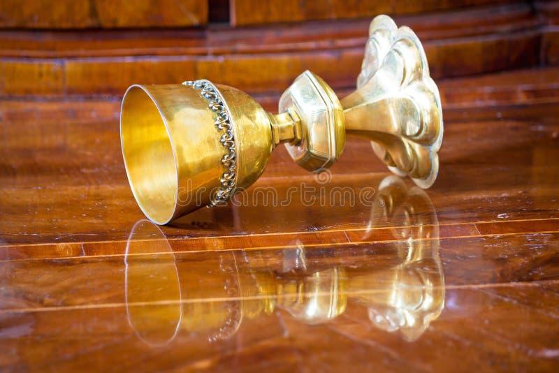 Guld- gral som vänds på träbakgrund royaltyfria foton