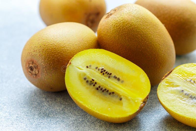 Guld- gul organisk kiwi Hela och för snitt mogna saftiga frukter på grå bakgrund kiwifruit arkivbild