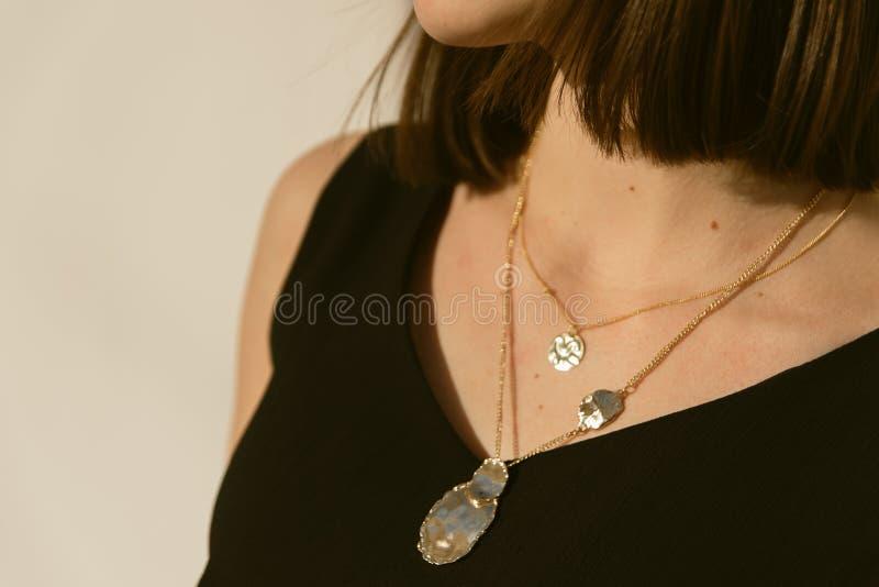 guld- hängear runt om halsen av en flicka i solen stilfulla modesmycken på personen royaltyfri foto