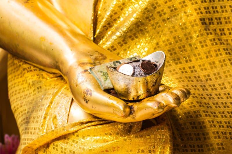 Guld- handbuddha staty med pengar royaltyfria bilder