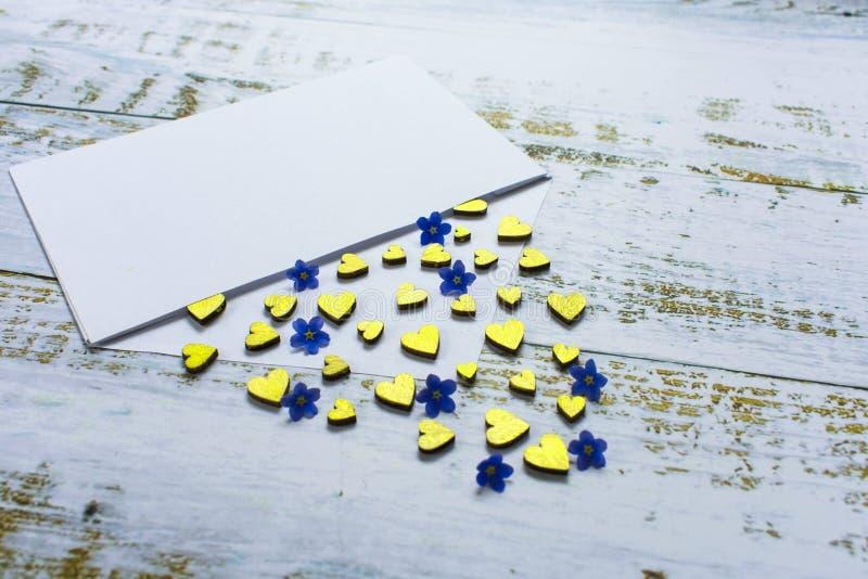 Guld- hjärtor och små blåa blommor i ett kuvert på en lila bakgrund valentin f?r dag s förälskelsebegreppsgåva, meddelande för vä arkivbilder