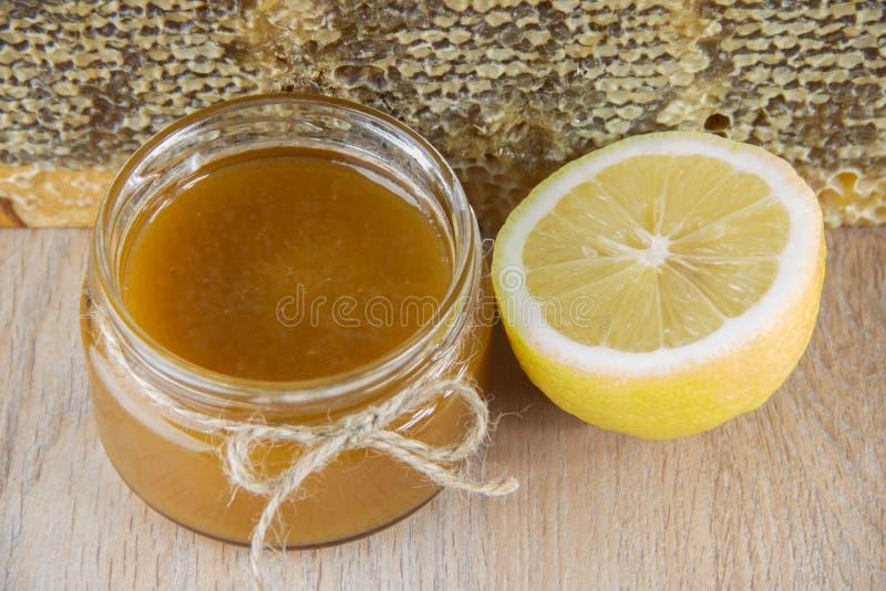 Guld- honung i hårkammen i en krus och en guling skivade citronen arkivbilder