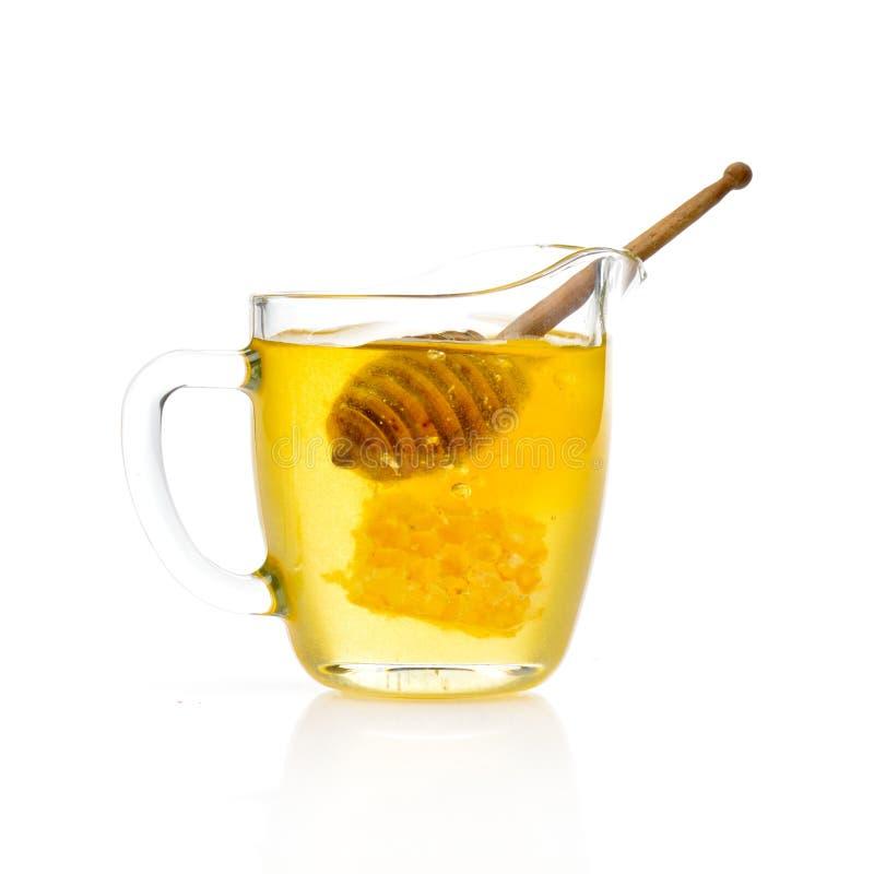 Guld- honung och träpinne i exponeringsglaset royaltyfri foto
