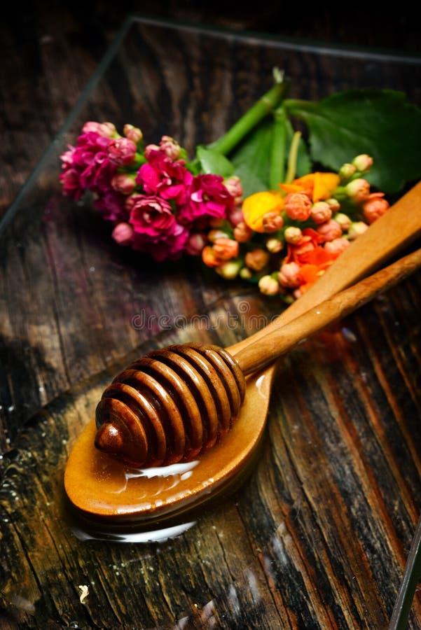 Guld- honung på plattan och blommor royaltyfri foto